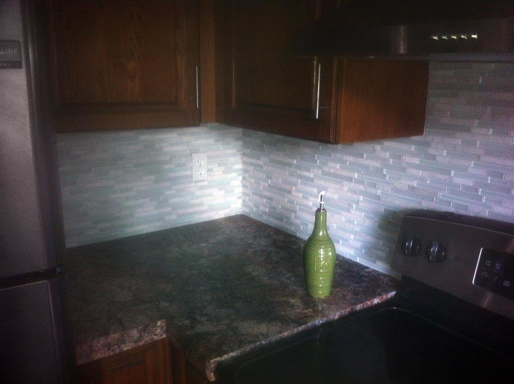 Glass tile softens the dark colors in this kitchen.
